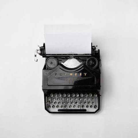 Old, black typewriter on a white background