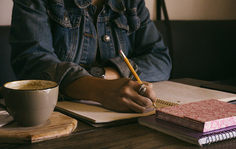 Person, sitting at a desk, making notes in a journal with a cup of coffee next to her