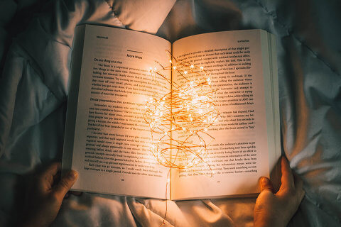 Reel of lights lying on an open book, held open by someone
