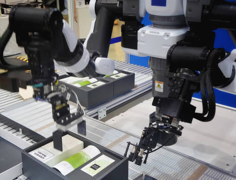 Robotic arms handling products on the factory line
