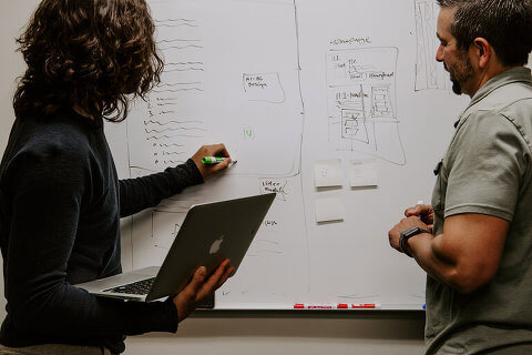 Two people working at a whiteboard, discussing an idea