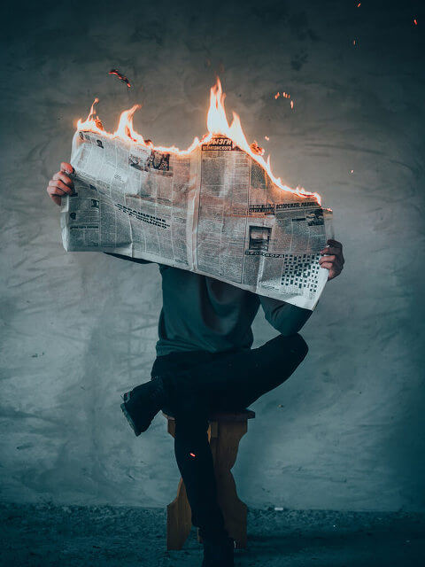 Person, sitting on stool, reading burning newspaper